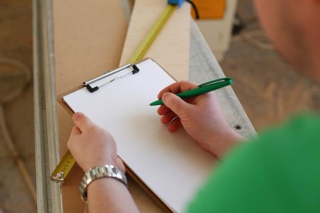 Braços de trabalhador, fazendo anotações na área de transferência com caneta verde