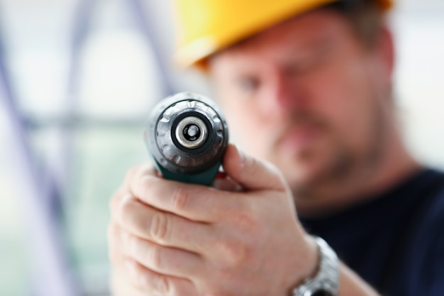 Braços de trabalhador usando furadeira elétrica closeup