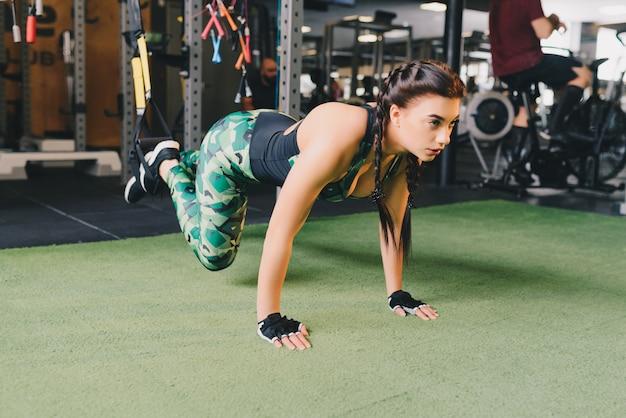Braços de treinamento de mulher com tiras de trx fitness no ginásio fazendo flexões treinar parte superior do corpo ombros ombros pecs tríceps.