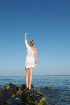 Braços estendido da jovem mulher da liberdade na borda do penhasco da rocha do beira-mar.
