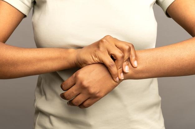 Braços femininos negros massageando o pulso dolorido, sofrendo de fraqueza e formigamento por lesão esportiva
