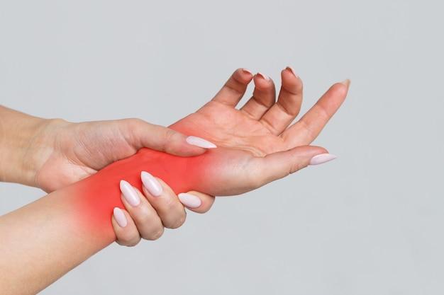 Braços femininos segurando o pulso dolorido causado por trabalho prolongado no computador