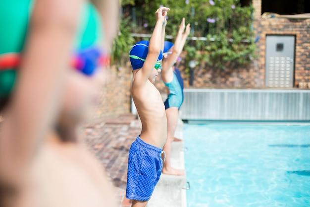 Braços levantados, pequenos nadadores em pé à beira da piscina