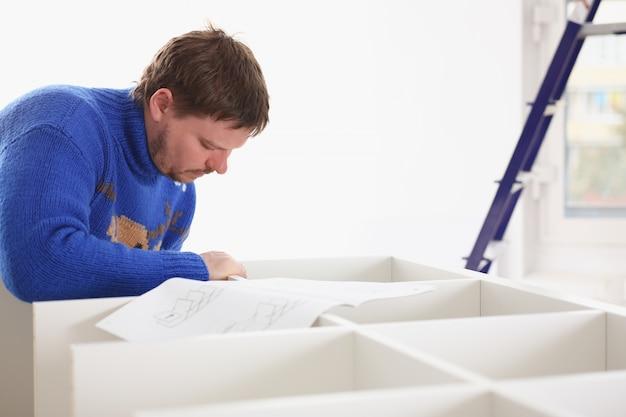 Braços masculinos, montagem de móveis closeup