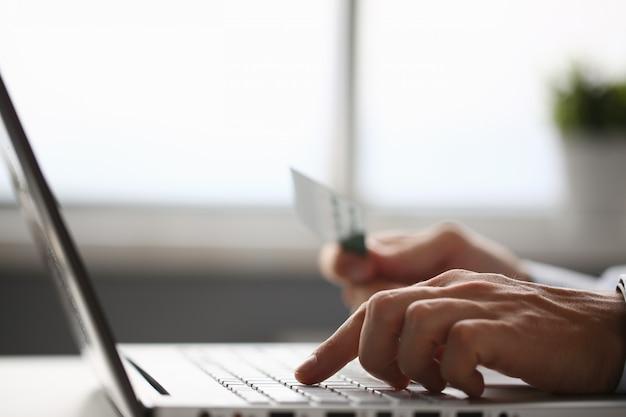 Braços masculinos segurar botões de imprensa de cartão de crédito fazendo