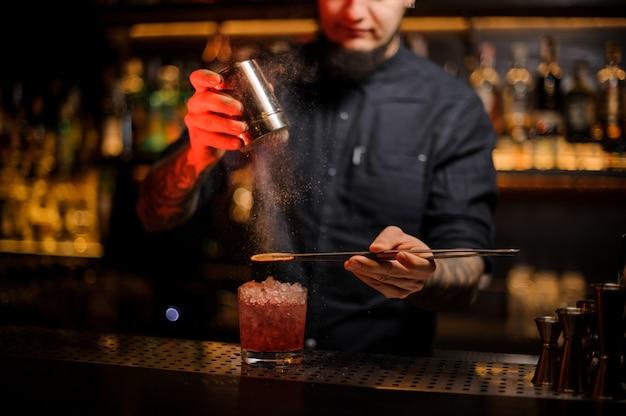 Braga, adicionando especiarias em pó em um copo de cocktail