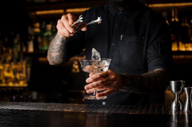 Braga, colocando um cubo de gelo em um copo de cocktail