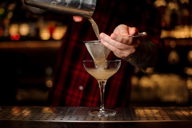 Braga, derramando cocktail alcoólico suculento da coqueteleira em copo de cocktail