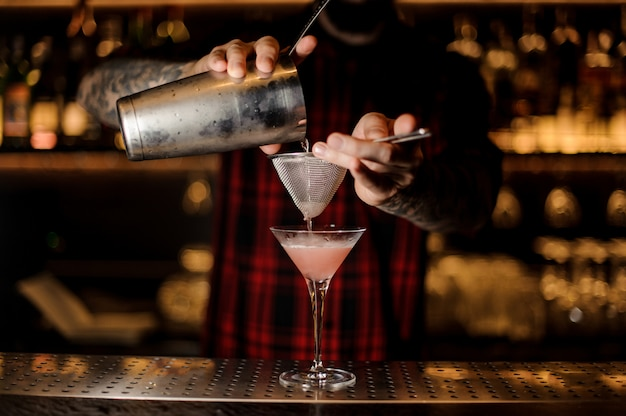 Braga, derramando um cocktail cosmopolita em um copo