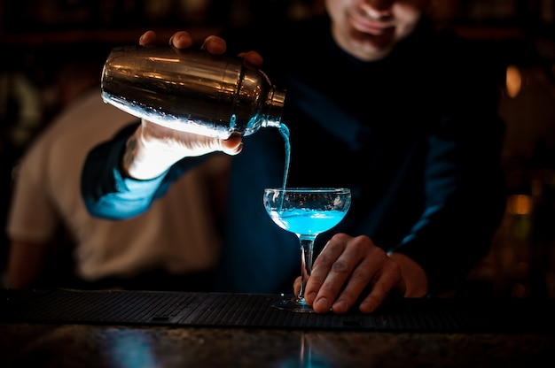 Braga, derramar bebida fresca com licor azul de um agitador em um copo usando filtro a sorrir