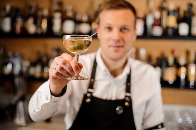 Braga, segurando um copo cheio de bebida alcoólica com azeitonas