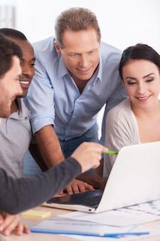 Brainstorming da equipe criativa. grupo de empresários em trajes casuais sentados juntos à mesa e discutindo algo enquanto olham para o laptop