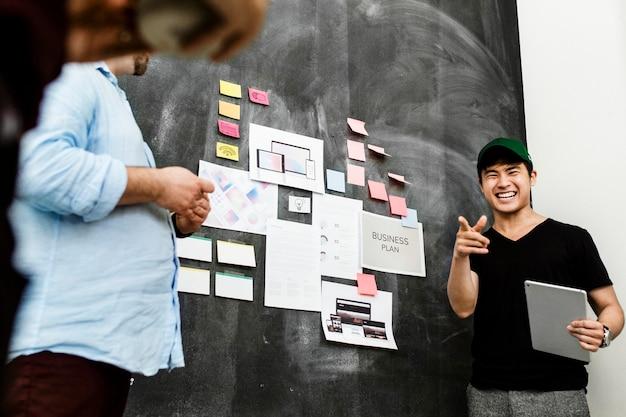 Brainstorming da equipe de inicialização na sala de reuniões usando o quadro-negro