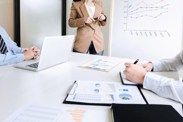 Brainstorming da equipe de negócios discutindo o desempenho da venda no quadro branco durante a apresentação