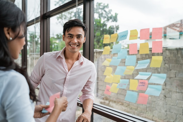 Brainstorming de parceiro de negócios, colocando a ideia na janela de vidro