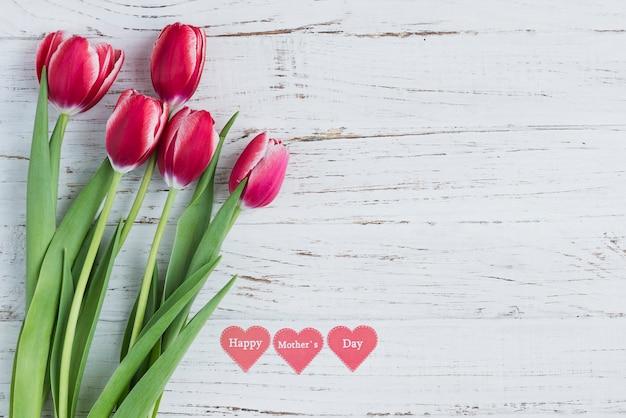 Branca superfície de madeira com tulipas e corações para o dia de mãe