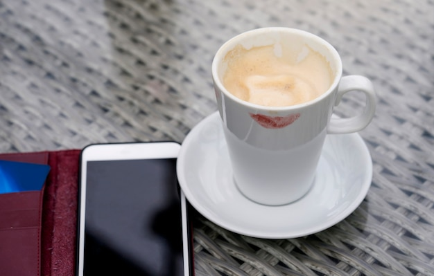 Branca, xícara café quente, com, marca, lábios, e, telefone móvel, ligado, a, tabela