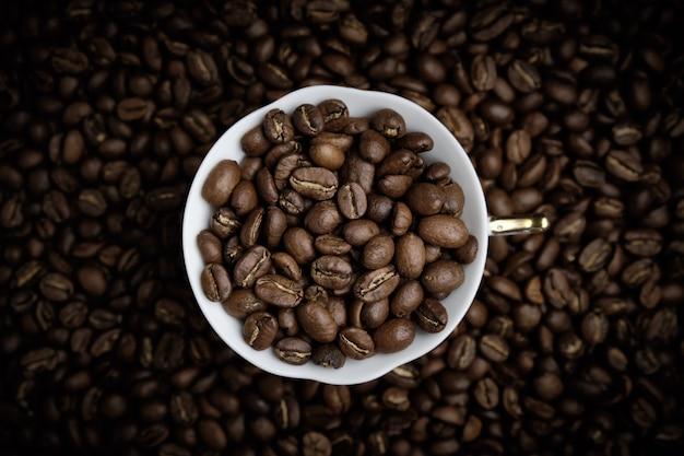 Branca xícara de café cheia de grãos de café. vinheta. vista do topo.
