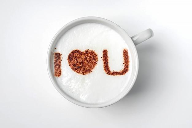 Branca xícara de café com a inscrição na espuma - eu te amo.