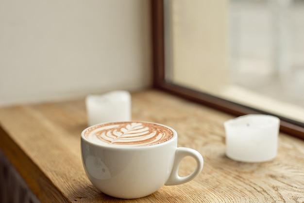 Branca xícara de café com leite com um padrão na espuma de leite em um peitoril da janela de madeira