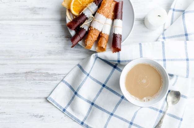 Branca xícara de café com leite e pastilha de frutas e batatas fritas