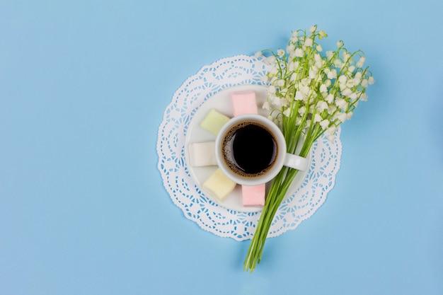 Branca xícara de café com leite em um pires, marshmallow, um buquê de flores de lírio do vale em fundo azul