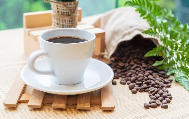 Branca xícara de café preto ou chá na placa de madeira sobre o feijão de café turva