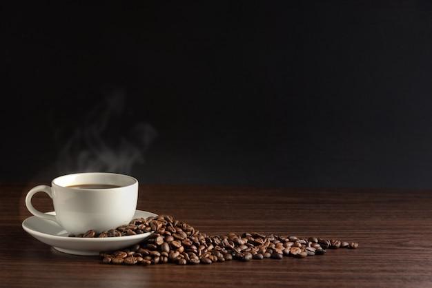 Branca xícara de café quente com fumaça com grãos de café e em fundo preto