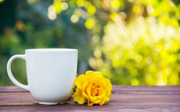 Branca xícara de chá na mesa de madeira, na hora do chá ao ar livre