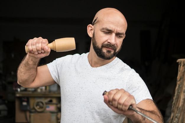 Branco careca carpinteiro com barba em t-shirt branca funciona como um formão e um malho
