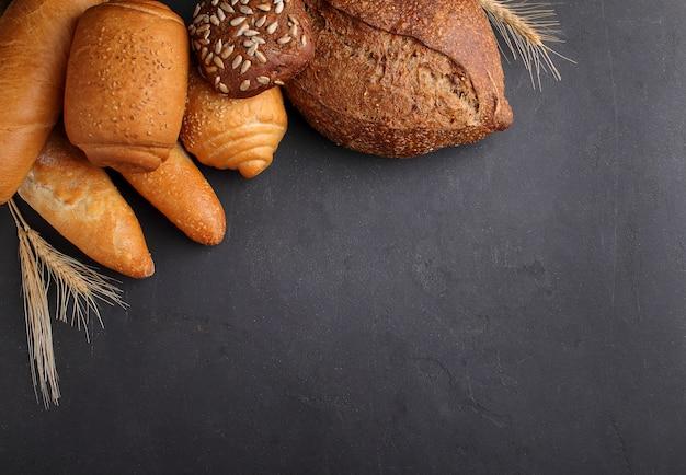Branco, cinza e pão de centeio, baguete, rolo com sementes de gergelim em um fundo preto