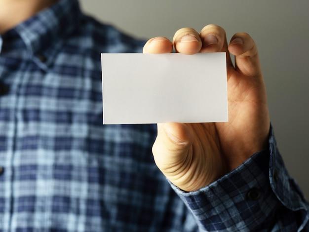 Branco colorido. um homem com uma camisa xadrez coloca um cartão de visita no bolso da camisa. copie o espaço