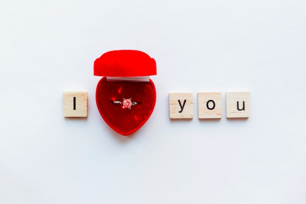 Branco com palavras de madeira eu te amo e anel de noivado de diamante na caixa de presente vermelha.
