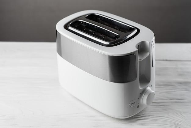 Branco com torradeira prata na parede cinza na mesa de madeira branca