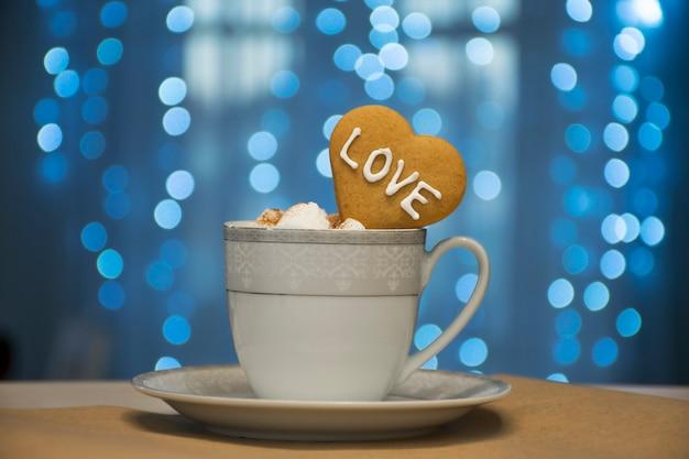 Branco com xícara de café de prata com marshmallow e biscoito de coração com palavra de amor em luzes azuis de fadas