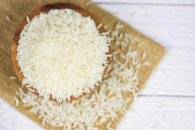 Branco de arroz tailandês na tigela de madeira e os produtos agrícolas de grãos de arroz de saco / jasmim cru para alimentos na ásia
