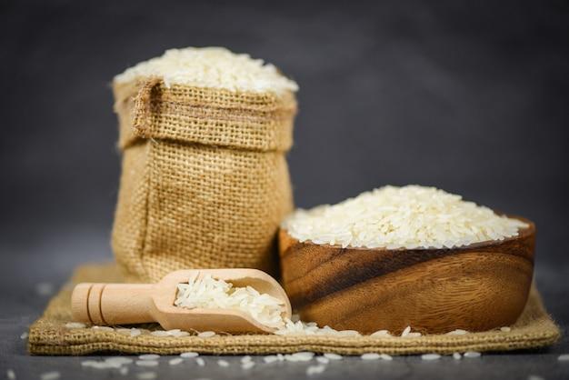 Branco de arroz tailandês na tigela e os produtos agrícolas de grãos de arroz de saco / jasmim cru para alimentos na ásia