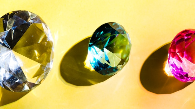 Branco; diamante de cristal verde e rosa em fundo amarelo
