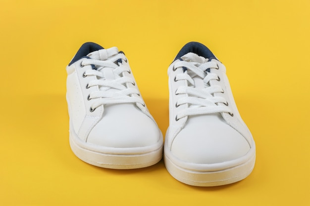 Branco esportes sapatos, tênis com cadarços em um fundo amarelo. conceito de estilo de vida de esporte