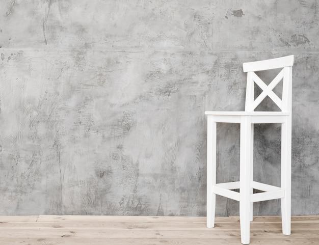 Branco minimalista e banquinho com painéis de concreto