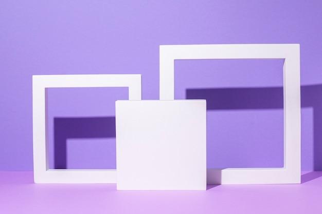 Branco quadrado e pódios de moldura para apresentações de pedestal em um fundo roxo.