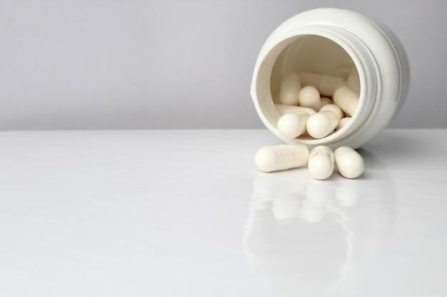 Brancos médicos comprimidos e comprimidos derramando fora de um frasco de drogas.