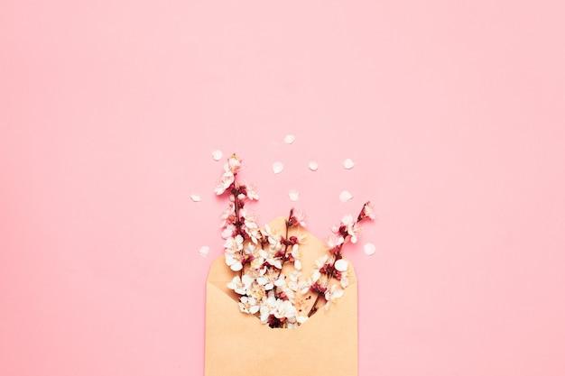 Brancos ramos floridos em envelope em fundo rosa