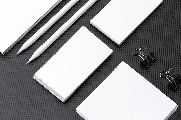 Branding mock up. artigos de papelaria incorporados em branco ajustados no papel preto.