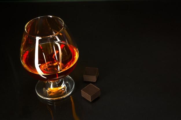 Brandy copo e chocolate no fundo preto