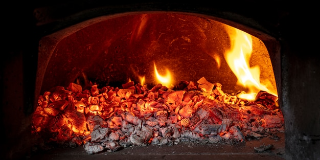 Brasas de madeira dentro de um forno a lenha