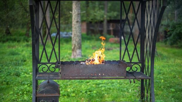 Braseiro de metal de ferro forjado antigo com um belo padrão no pátio