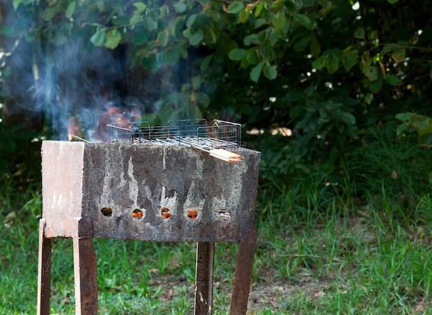 Braseiro sujo de metal velho enquanto cozinha um churrasco na floresta, europa oriental