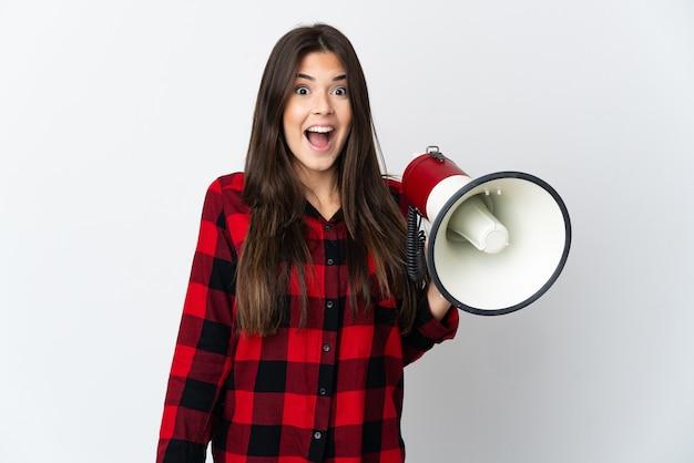 Brasileira adolescente isolada na parede branca segurando um megafone e com expressão de surpresa