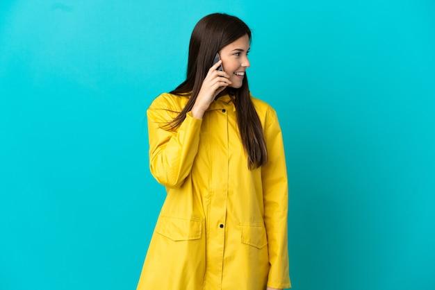 Brasileira adolescente vestindo um casaco à prova de chuva sobre fundo azul isolado, conversando com alguém com o telefone celular